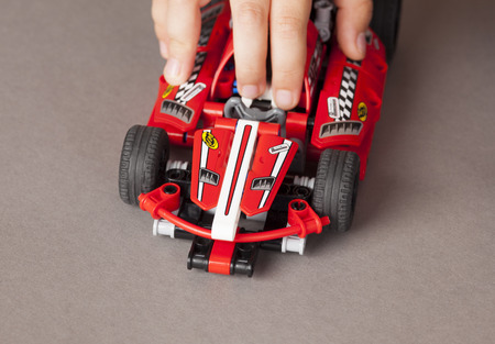 technic: Tambov, Russian Federation - July 01, 2013 Child hand with LEGO Technic Race Car. Item 42011. Ages 7-14. Studio shot. Technic is a line of Lego interconnecting plastic rods and parts. Technic sets are often characterized by the presence of special pieces, Editorial