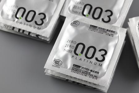 condones: Tambov, Rusia - 29 de agosto de Okamoto condones en fondos grises. En esta demostración de la foto condones Okamoto 003 Platinum.