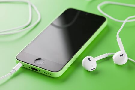 Tambov, Russian Federation - October 16, 2013 Apple iPhone 5C Green Color with new Apple EarPods on green background. Studio shot. iPhone 5C is produced by Apple Computer, Inc. Editorial