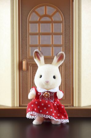animal figurines: Tambov, Russian Federation - October 04, 2013 Sylvanian family rabbit-mother toy figure in red dress standing in front of the door of her house. Studio shot. Sylvanian Families is a line of collectible anthropomorphic animal figurines made of flocked pl