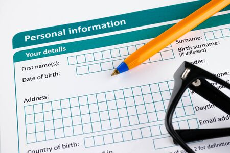Personal information form with ballpoint pen and glasses.