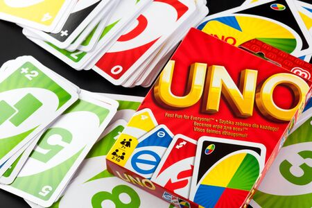 Tambov, Russian Federation - August 15, 2013 Cards of UNO game and UNO game box on black background. Studio shot.