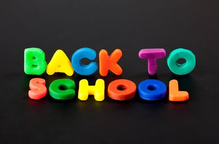 child's play clay: Words Back to school on black background. Letters made of childs play clay.