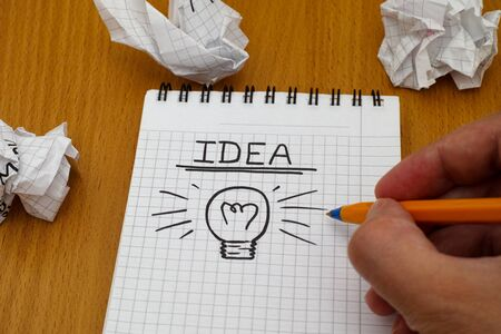 writing paper: Human hand written word Idea and light bulb on white note pad with ballpoint pen and crumpled paper balls. Stock Photo