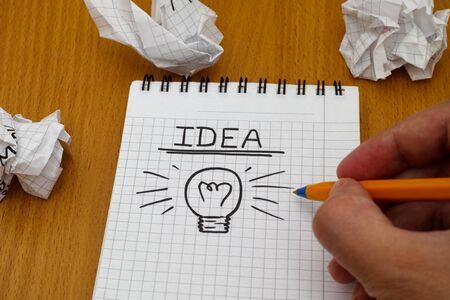 Menselijke hand geschreven woord Idee en gloeilamp op wit notitieblok met balpen en proppen papier ballen. Stockfoto