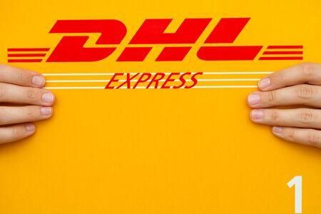Tambov, Russian Federation - June 01, 2015 DHL Express package in human hands. Studio shot.