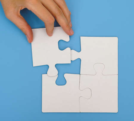 final piece of puzzle: Woman hand putting the final piece to complete simple puzzle on blue background Stock Photo