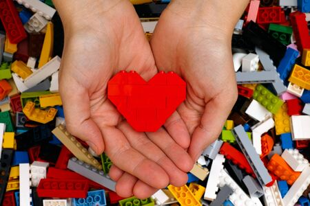 Tambov, Russian Federation - September 07, 2015 Lego red heart in woman hands with Lego blocks background. Studio shot.