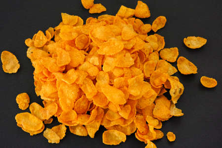 black background: Heap of corn flakes on black background