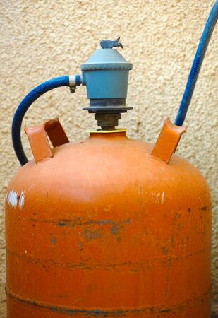regulator: Orange gas bottle with gas regulator.