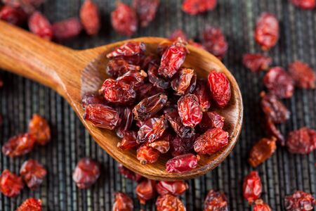 barberry: Dry barberry in a wooden spoon on black napkin. Stock Photo