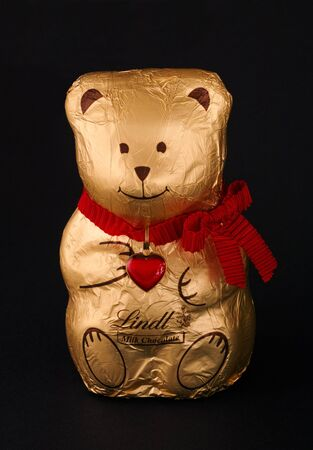lindt: Paphos, Cyprus - December 10, 2015 Lindt Milk Chocolate Bear in gold foil with heart on red ribbon. Black background.