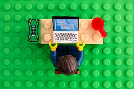 탐 보프, 러시아 - 2015 년 3 월 24 일 레고 사업가 레고 녹색 밑판 배경에 컴퓨터, 돈 및 컵 그의 작업 테이블에 앉는 다. 평면도. 스튜디오 촬영.