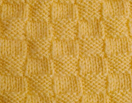 needlecraft product: Yellow hand knitted texture. Close-up.