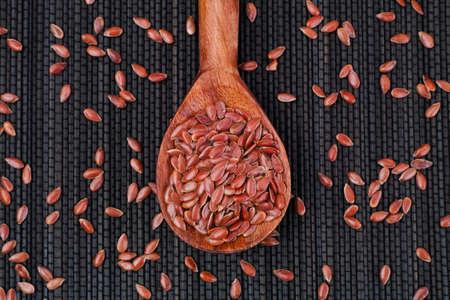 organic flax seed: Organic flax seeds in wooden spoon on black napkin.