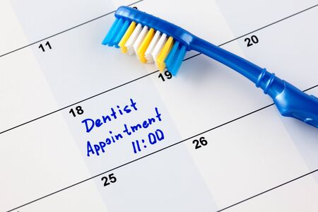 reminder: Reminder Dentist appointment 11-00 in calendar with toothbrush. Stock Photo