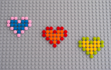 yellow lego block: Tambov, Russian Federation - January 24, 2016 Three Lego hearts from Round Bricks 1x1 on Lego gray baseplate. Studio shot. Editorial