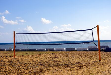 volleyball net: Beach volleyball net with sky and sea behind.