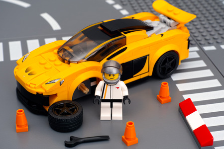 yellow lego block: Tambov, Russian Federation - March 04, 2015 Lego driver minifigure near his car McLaren P1 with broken wheel by LEGO Speed Champions on the Lego road baseplates. Studio shot. Editorial
