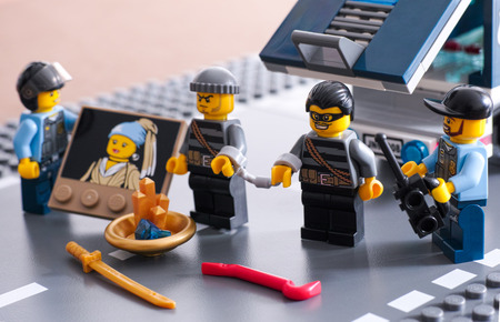 loot: Tambov, Russian Federation - September 03, 2014 Lego  arrest. Two police officers and two robbers in handcuffs with loot near police car. Studio shot.