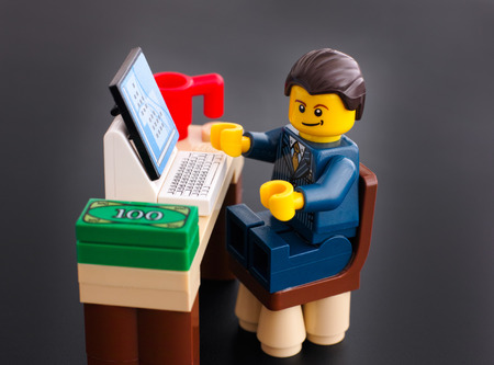 businessman working at his computer: Tambov, Russian Federation - March 24, 2015 Lego businessman sits at his working table with computer, money and cup on black background. Studio shot.