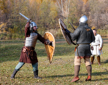 panoply: Tambov, Russian Federation - October 12, 2014 Two warriors in old Russian armors reconstructed medieval fight with swords and shields on the battlefield.