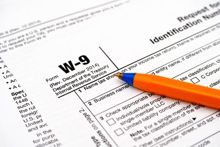 taxpayer: Form W-9, Request for Taxpayer Identification Number (TIN) and Certification with pen Stock Photo