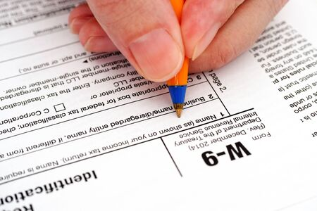 taxpayer: Person hand with pen filling in form W-9, Request for Taxpayer Identification Number (TIN) and Certification