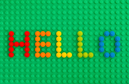 yellow lego block: Tambov, Russian Federation - January 24, 2016 Word Hello spell out from Lego Round Bricks 1x1 on green baseplate. Studio shot.