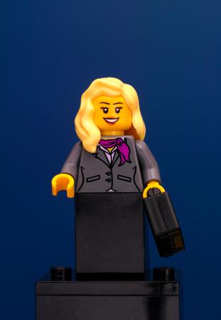 Tambov, Russian Federation - June 08, 2015 Lego businesswoman minifigure with black suitcase on blue background. Studio shot.