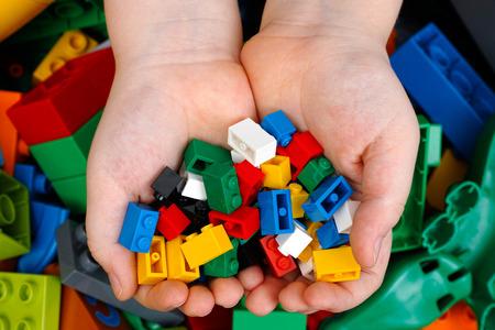 Tambov, Rusland - 20 februari 2015 Lego Bakstenen in Childs handen met Lego Duplo blokken en speelgoed achtergrond. Studio-opname.