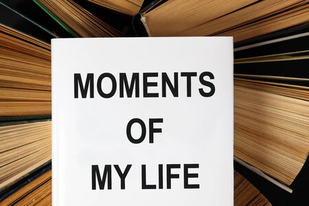 hardback: Top view of old hardback books with book Moments of my life. Stock Photo