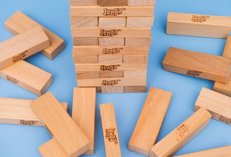 constructed: Tambov, Russian Federation - March 03, 2016 Jenga tower constructed and some blocks on blue background. Studio shot.