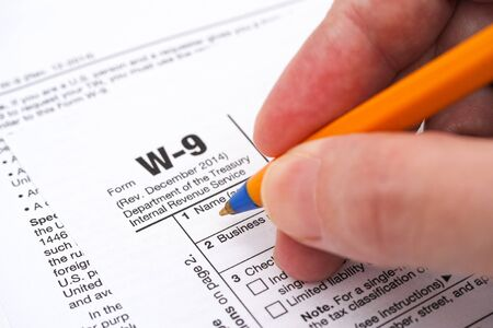 Person hand with ballpoint pen filling in form W-9, Request for Taxpayer Identification Number (TIN) and Certification