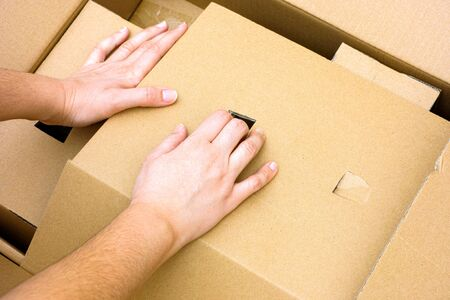 cardboard: Woman hands unpacking big cardboard box.