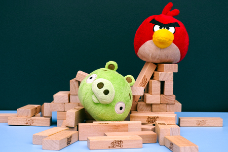 bird       s house: Tambov, Russian Federation - March 03, 2016 Angry Bird vs. Bad Piggies. Red bird broke bad pig's house. Bad piggy lying in pile of Jenga bricks which its house was made out of.. Studio shot. Editorial