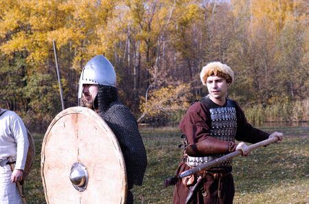 middleages: Tambov, Russian Federation - October 12, 2014 Two warriors in old Russian armors reconstructed medieval fight with spear, sword and shield on battlefield.