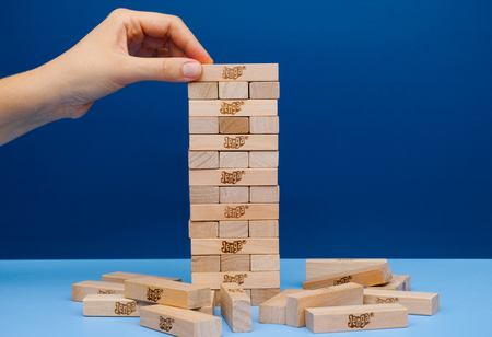 constructed: Tambov, Russian Federation - March 03, 2016 Player hand build Jenga tower constructed. Blue background. Studio shot.