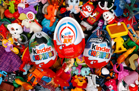 kinder: Tambov, Russian Federation - March 25, 2016 Big heap of Kinder Surprise toys wih Kinder Surprise and Kinder Joy eggs. Kinder Surprise manufactured by Italian company Ferrero. Studio Shot. Each Kinder Surprise egg consists of a chocolate shell, a plastic c