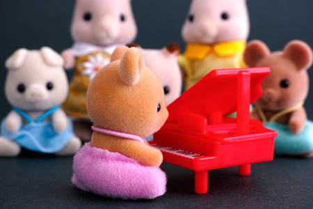 critters: Tambov, Russian Federation - April 01, 2016 Sylvanian family piano concert. Deer Baby sits by red piano in front of audience. Studio shot. In Canada and the USA Sylvanian family famous us Calico Critters.