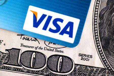 tarjeta visa: Tambov, Rusia - 02 de abril de, el año 2016 logotipo de Visa en la tarjeta de crédito y el billete de 100 dólares. estudio de disparo.