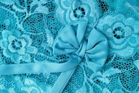 celadon blue: Aquamarine lace with bow background. Close up.