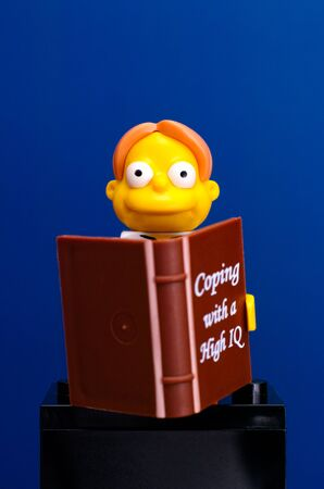 coping: Tambov, Russian Federation - June 08, 2015 Lego Martin Prince (The Simpsons Movie) minifigure with book on blue background. Studio shot.