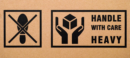 handle with care: Signs Do not step and Handle with care Heavy on cardboard box Stock Photo
