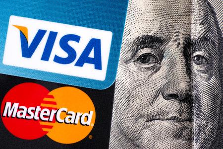 one hundred dollar bill: Tambov, Russian Federation - April 02, 2016 Visa and MasterCard logo on credit cards on one hundred dollar bill with Benjamin Franklin portrait. Studio shot.