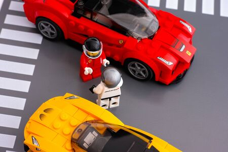yellow lego block: Tambov, Russian Federation - March 09, 2015 Lego drivers standing in front of each other by LEGO Speed Champions and his car. There are Lego LaFerrari and Lego McLaren P1 cars models. Studio shot. Editorial