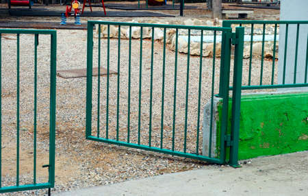 open gate: Open gate to playground. Focus is on the ground.