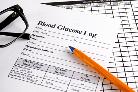 blood glucose: Blood Glucose Log and Monthly Blood Glucose Monitoring Diary forms with ballpoin pan and glasses. Stock Photo