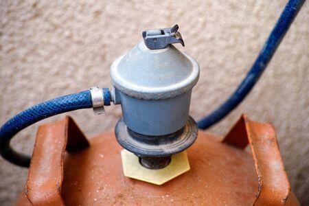regulator: Gas regulator switch on orange gas bottle.