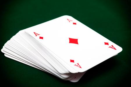 Deck von Karten mit Ass des Diamanten an der Spitze. Grüner Hintergrund